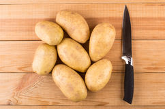 Heap of raw washed potatoes and kitchen knife Stock Image