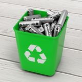 Heap of Rechargeable Batteries in Green Bucket with Recycle Sign. On a wooden table. 3d Rendering Stock Images