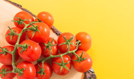 Heap of red cherry tomatoes with stem on wood Stock Images