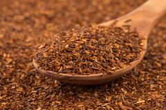 Heap of dry rooibos tea. Heap of red dry rooibos healthy traditional organic tea in spoon Royalty Free Stock Images