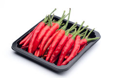 Heap of red hot chili pepper in black container on white backgro Stock Photos