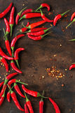 Heap of red hot chili peppers. Frame board of fresh red hot chili peppers over old wooden textured background. Spicy theme. Top view Royalty Free Stock Photography