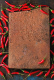 Heap of red hot chili peppers. Frame of fresh red hot chili peppers with empty clay board in center over old wooden textured background. Spicy theme. Top view Royalty Free Stock Image