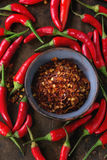 Heap of red hot chili peppers. Heap of fresh red hot chili peppers with ceramic bowl of dry chilli flakes over old wooden textured background. Spicy theme. Top Stock Images