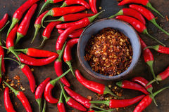 Heap of red hot chili peppers. Heap of fresh red hot chili peppers with ceramic bowl of dry chilli flakes over old wooden textured background. Spicy theme. Top Royalty Free Stock Photo