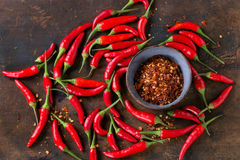 Heap of red hot chili peppers. Heap of fresh red hot chili peppers with ceramic bowl of dry chilli flakes over old wooden textured background. Spicy theme. Top Royalty Free Stock Image