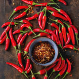 Heap of red hot chili peppers. Heap of fresh red hot chili peppers with ceramic bowl of dry chilli flakes over old wooden textured background. Spicy theme. Top Royalty Free Stock Photos