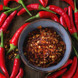 Heap of red hot chili peppers. Heap of fresh red hot chili peppers with ceramic bowl of dry chilli flakes over old wooden textured background. Spicy theme. Top Stock Photos
