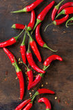 Heap of red hot chili peppers. Heap of fresh red hot chili peppers over old wooden textured background. Spicy theme. Top view Stock Image