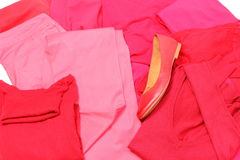 Heap of red and pink clothes with womanly shoes Stock Photos