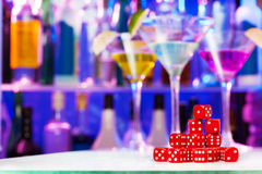 Heap of red playing dices, bar bottles and glasses Stock Image