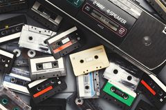 Heap of vintage audio cassettes and tape recorder at gray background Royalty Free Stock Photography