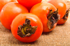 Heap of riipe persimmon fruits on sacking background Royalty Free Stock Photography