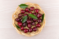 Heap of ripe cherries with leaves in wicker basket. On table, top view Stock Image