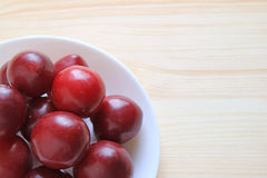 Heap of Ripe Gulf Ruby Plum Fruits Piled Up on White Plate on Wooden Table, Close-Up Stock Images