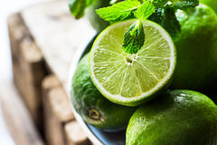Heap of ripe organic limes cut in half in the sunlight, leaves o Stock Image