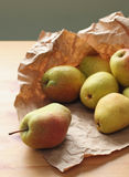 Heap of ripe pears on wooden table rapped in paper Stock Photo