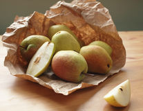 Heap of ripe pears on wooden table rapped in paper Stock Photos