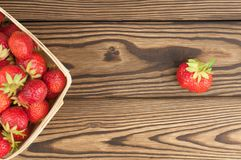 Heap ripe strawberries in wicker basket and single. On old rustic wooden planks royalty free stock photography