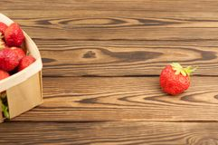 Heap ripe strawberries in wicker basket and single. On old rustic wooden planks stock image