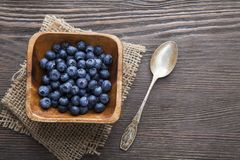 Heap ripe sweet blueberries and spoon on wooden table top view.  Stock Photo