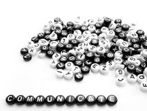 Heap of round letters black and white and communicate word written by side Stock Photography