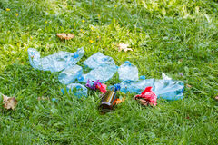 Heap of rubbish on grass in park, littering of environment Stock Photo