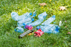 Heap of rubbish on grass in park, littering of environment Royalty Free Stock Image