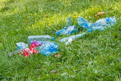Heap of rubbish on grass in park, littering of environment Stock Photography