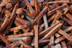 Heap of Rusted Railroad Spikes. A heap of discarded, rusting railroad spikes lies on the ground Stock Images