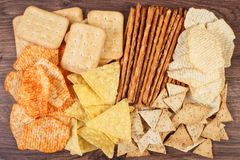 Heap of salted crisps, breadsticks and cookies, concept of unhealthy food. Heap of crunchy potato crisps, breadsticks and cookies on rustic board, concept of royalty free stock image