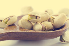 Heap salted pistachio nuts on wooden spoon background, vintage color Stock Photos