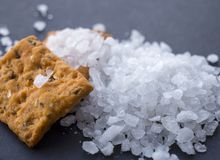 Heap of sea salt and salty crackers. Black surface. Food photography stock photo