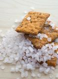 Heap of sea salt and salty crackers. Wooden surface. Food photography royalty free stock images