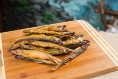 Heap of small fresh fish. Heap of small fresh anchovies, fish, sardines close-up sacking and blue background Stock Photos