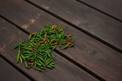 Heap of small green and red chili peppers on wooden background royalty free stock photo