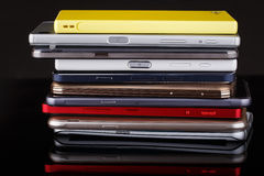 Heap of smartphones. Heap of electronical devices close up - smartphones on black background Royalty Free Stock Photos