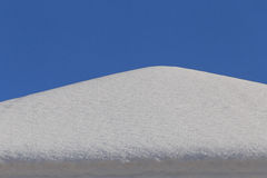 Heap of snow on roof. Over blue sky Stock Photo