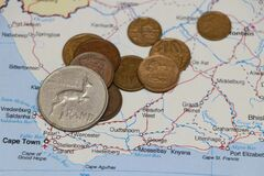 Heap of South African Rand coin money on on the map. Concept of finance or travel
