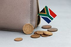 Heap of South African Rand coin money and mini South African flag stick on the leather wallet on grey background