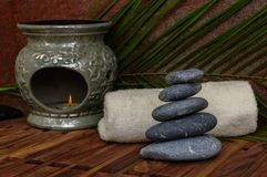Heap of spa hot stones for massage with aroma lamp on wooden background. Heap of spa hot stones for massage with aroma lamp and palm leaves on wooden background Stock Photography