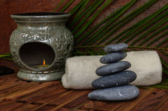 Heap of spa hot stones for massage with aroma lamp on wooden background. Heap of spa hot stones for massage with aroma lamp and palm leaves on wooden background Royalty Free Stock Photos