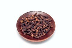 Heap of spice cloves on a wooden plate, isolated on white backgr royalty free stock photo