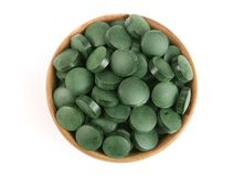 Heap of Spirulina tablets algae nutritional supplement in wooden bowl isolated on white background close up top view. Flat lay Royalty Free Stock Images
