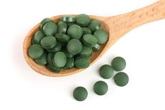 Heap of Spirulina tablets algae nutritional supplement in wooden spoon isolated on white background close up top view. Flat lay Stock Images