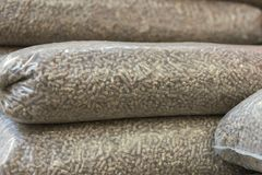 Heap of stacks of Pine pellets - stock image. Eco pellets- biomass in bags.  royalty free stock photography