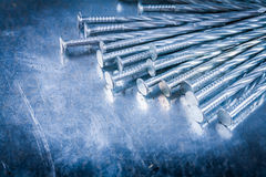 Heap of stainless construction nails on scratched metallic surfa Stock Photo