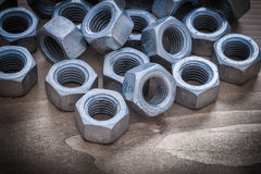 Heap of steel threaded construction nuts on vintage wooden surfa Stock Photography