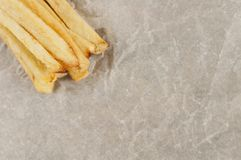 Heap of sticks of french fries on gray crumpled paper. Top view stock photo