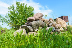 Heap of stones on the grass and brazier on background Royalty Free Stock Photos